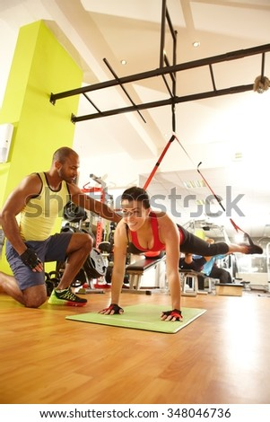 Sporty woman doing TRX suspension training with the guidance of coach. - stock photo