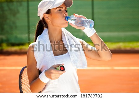 sporty woman drinking water after tennis training - stock photo