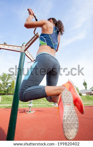 sporty woman exercising outdoor on sunny day - stock photo