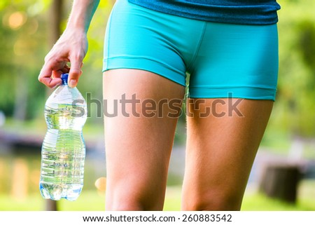 Sporty woman holding bottled water after exercising - stock photo