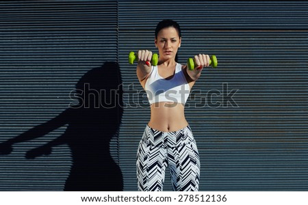 Sporty woman holding weights with hands up at her front getting arms in great shape,sexy female with beautiful figure working out lifting dumbbells against black copy space background for text message - stock photo