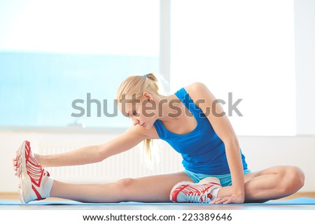 Sporty woman in activewear doing stretching exercise in gym - stock photo
