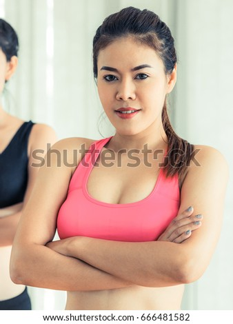 Sporty woman in fitness gym, arm crossed, looking at camera. Healthy lifestyle and wellness concept.