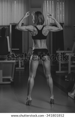 Sporty woman in gym.Beautiful muscular fit woman exercising building muscles.Nice sexy woman doing workout in gym.