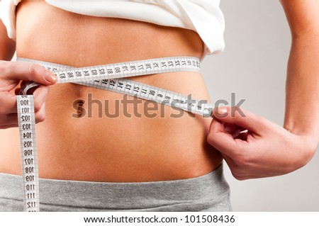 sporty woman is measuring her waist on grey background