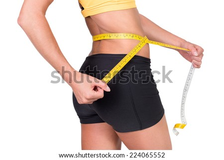 Sporty woman measuring her slim body. Isolated on white. Healthy lifestyle concept. - stock photo