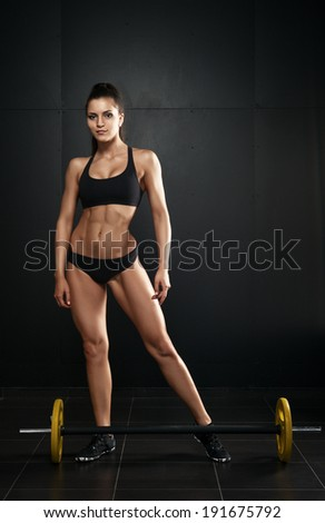 sporty woman on dark background with dumbbells - stock photo