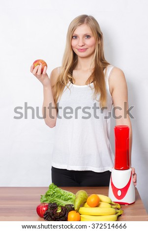 Sporty woman preparing smoothie, blender and fruits on table - stock photo