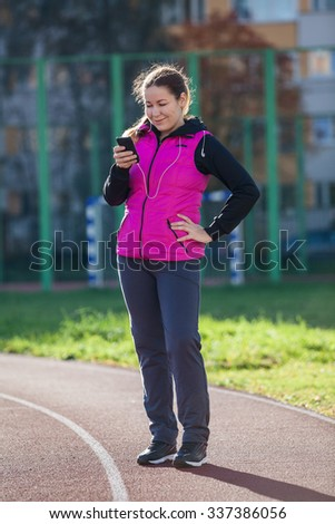 Sporty woman reading message with mobile phone while standing at the running track of the stadium - stock photo