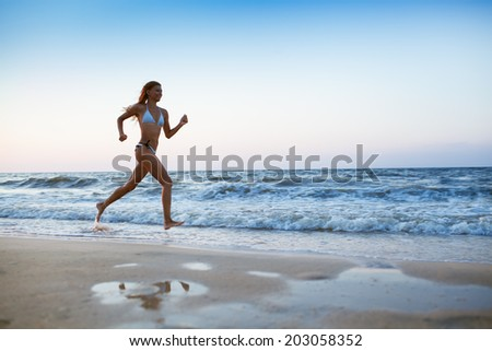 sporty woman run at sea cost on sunset - stock photo