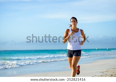 Sporty woman running by the sea on tropical beach during caribbean vacation. Fitness and healthy lifestyle on summer holidays. - stock photo