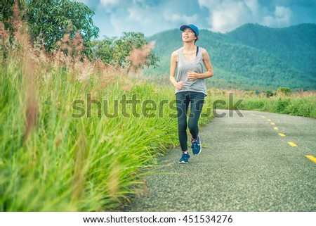 Sporty woman running on road at sunrise. Fitness and workout wellness concept.