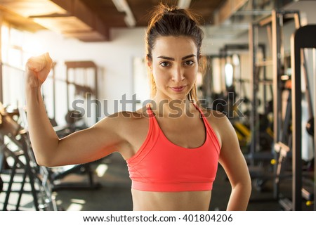 Sporty woman showing her biceps in gym. - stock photo