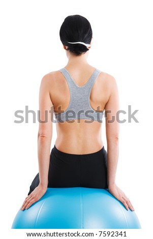 Sporty woman sitting on a ball, rear view - stock photo
