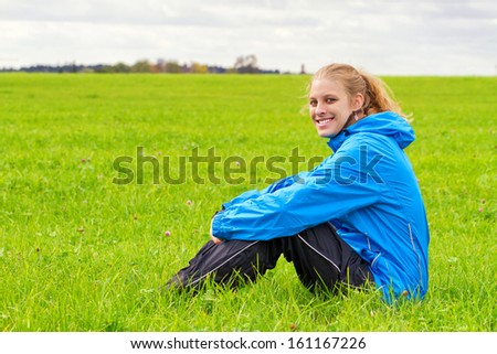 Sporty woman sitting on a meadow