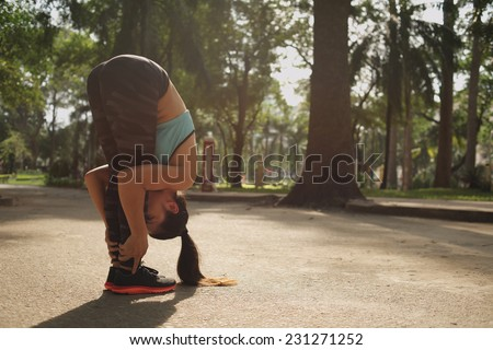 Sporty woman sportswoman doing a standing forward bend in the park  - stock photo