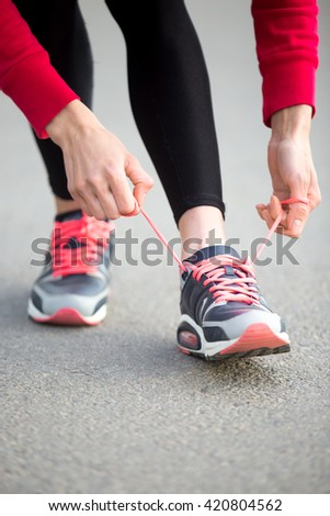 Sporty woman tying shoelace on sneakers before training. Female athlete preparing for jogging outdoors. Runner getting ready for morning running routine. Sport active lifestyle concept. Close-up - stock photo