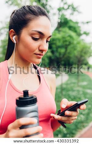 Sporty woman using smart phone after running - stock photo