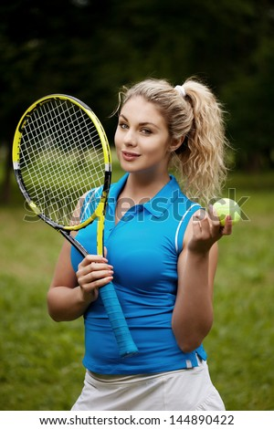 Sporty woman with a tennis-racket plays tennis - stock photo