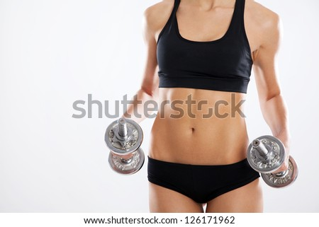 Sporty woman with dumbbells studio photo - stock photo