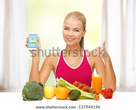 sporty woman with fruits and vegetables showing smartphone - stock photo