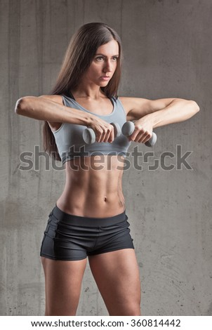 sporty woman with perfect body doing exercise with dumbbells - stock photo