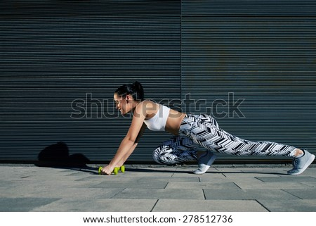 Sporty woman with perfect figure and buttocks shape stretching legs with dumbbells near copy space wall for your text message, fit female in workout gear doing push-ups on black background outdoors - stock photo