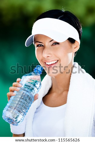 Sporty woman with plastic bottle of water after tennis training - stock photo