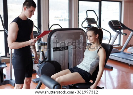 sporty woman with trainer exercise weights lifting in fitness gym