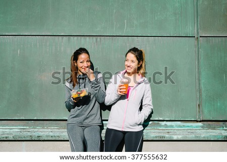 Sporty women eating healthy food after outdoor fitness workout. Fitness diet nutrition with fruit salad and carrot  orange detox smoothie. - stock photo