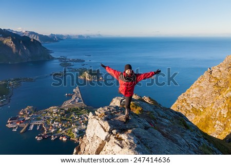 sporty women on the top of mountain over ocean, Reine fishing village, Lofoten, Norway - stock photo