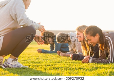 Sporty women planking during fitness class in parkland - stock photo