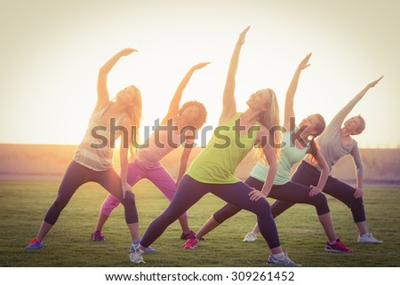 Sporty women warming up during fitness class in parkland - stock photo