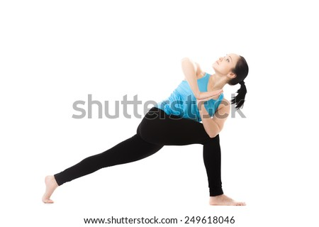 Sporty yoga girl exercises on white background in parivritta parshvakonasana (revolved side angle pose), palms in Namaste, isolated