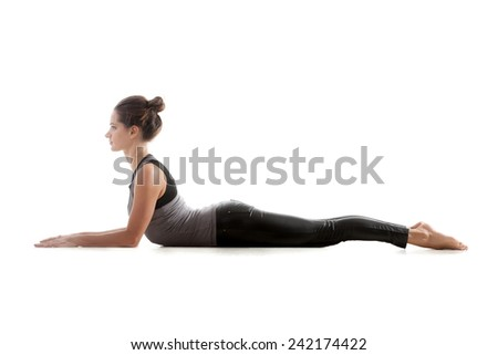 Sporty yoga girl on white background in bhudjangasana (Bhujangasana or Cobra Pose) - stock photo