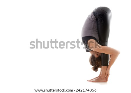 Sporty yoga girl on white background in uttanasana (Intense Forward-Bending Pose, Intense Stretch Pose, Forward Bend, Forward Fold Pose, Head to Knees Pose) - stock photo