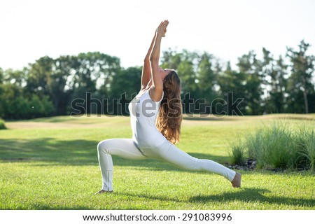 Sporty yogi brown-haired girl doing asana Anjaneyasana, low lunge yoga pose. Girl in sport suit training in the park. - stock photo