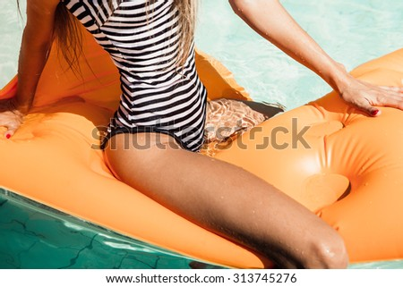 Sporty young beautiful female in a striped black and white swimsuit sits astride on an inflatable mattress in the refreshing pool. Outdoor lifestyle picture on a hot sunny summer day. - stock photo