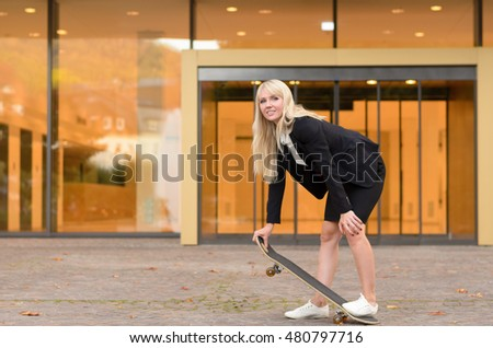Sporty young blond woman with a skateboard bending forward to hold the end as she stands on the back while looking at the camera in an urban setting