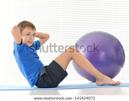 sporty young boy in a blue doing exercises on a white background