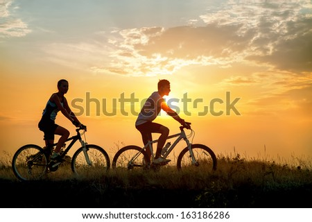 Sporty young couple on bicycles outdoors against sunset - stock photo