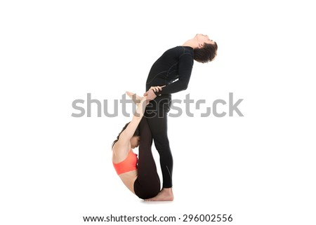 Sporty young couple on white background doing stretching exercises together, yoga, fitness or pilates practice with partner, studio shot, full length - stock photo