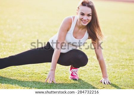 Sporty young female on a field sit in splits smiling while stretching. Friendly cheerful smile. Brightly lit photo - stock photo