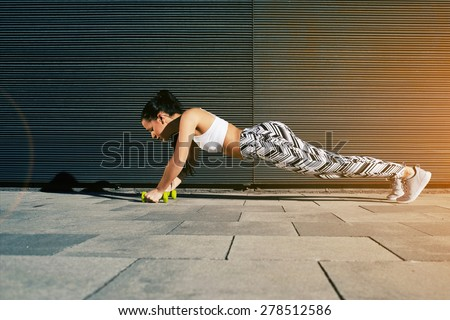 Sporty young woman doing press ups with dumbbells on black background outdoors, female in workout gear doing push-ups with some weights against wall with copy space for your text message, flare sun - stock photo