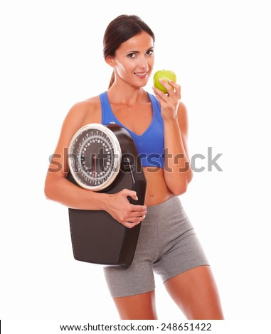 Sporty young woman eating apple to lose weight and looking at you against white background