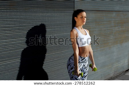 Sporty young woman holding weights with hands by sides against black wall background at sunset,attractive female look to you while working on her arms outdoors against copy space for your text message - stock photo