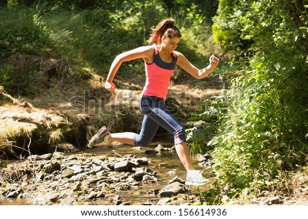 Sporty young woman leaping over a stream in a forest on a run - stock photo