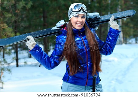 Sporty young woman posing with her skis outdoor.