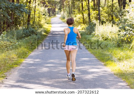 Sporty young woman runner running on the road in forest - stock photo