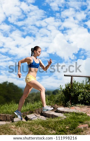 Sporty young woman running up stairs in park - stock photo